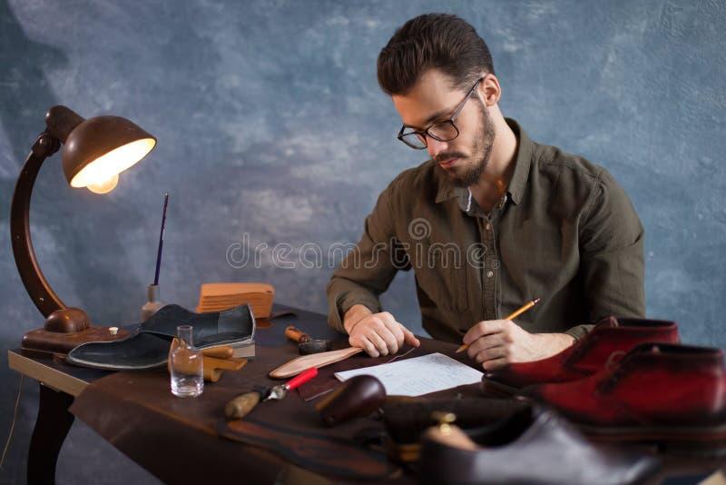 Vakman die een schets van de laarzen schrijven royalty-vrije stock afbeelding