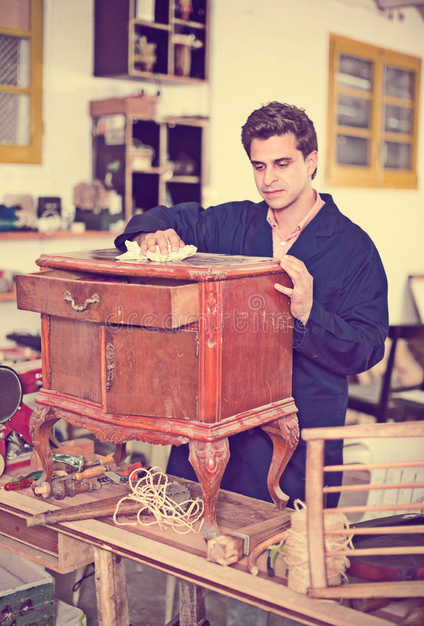 Vakman die nightstand vóór restauratie inspecteren stock foto
