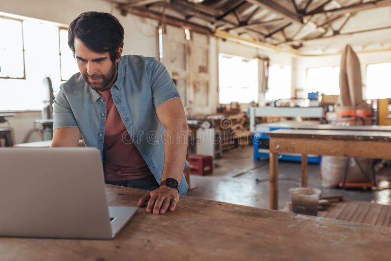 Vakman die online met laptop in zijn houtbewerkingswinkel werken stock afbeelding