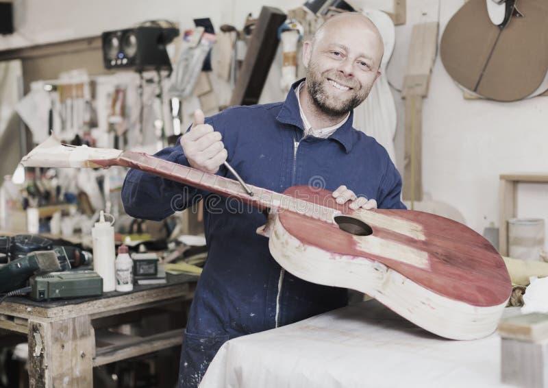 Vakman die onvolledige gitaar houden royalty-vrije stock afbeeldingen
