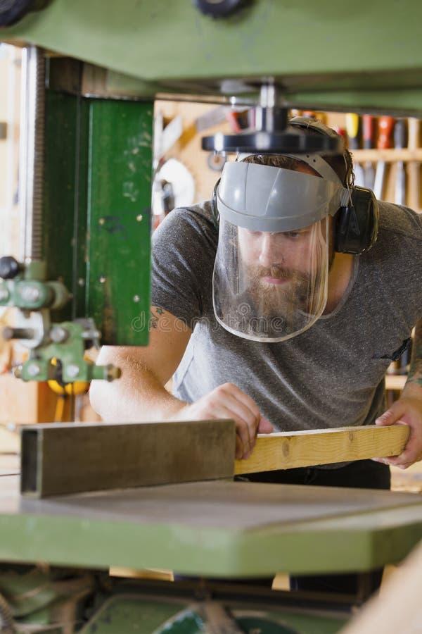 Vakman met de lintzaag van het vizierhandvatten van het veiligheidsmasker in workshop royalty-vrije stock fotografie