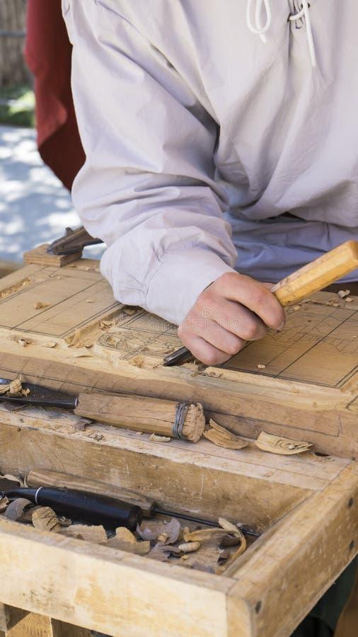 vakman snijdend hout in een middeleeuwse markt, timmerwerkhulpmiddelen royalty-vrije stock afbeelding
