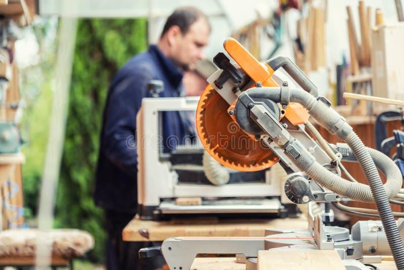 Vakmanhoutbewerking bij timmerwerk met veel moderne professionele machtshulpmiddelen Mens die thicknessing machine met behulp van stock afbeeldingen