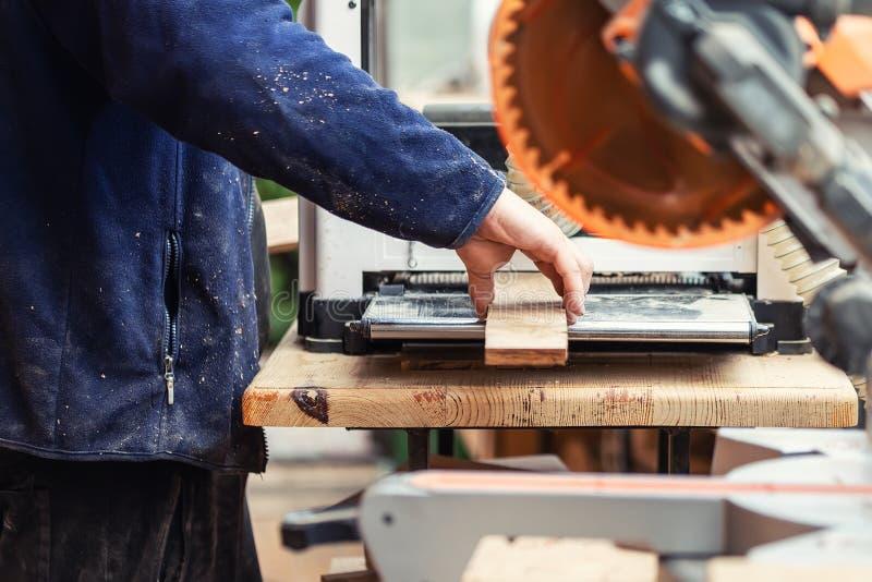 Vakmanhoutbewerking bij timmerwerk met veel moderne professionele machtshulpmiddelen Mens die thicknessing machine en cirkelzaag  stock afbeeldingen