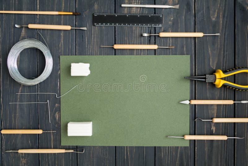 Vakmanwerkplaats, klaar voor het beeldhouwen van polymeerklei Uitstekende werkende lijst met het vormen van hulpmiddelen Vlak leg stock foto