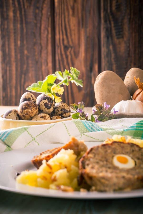 Vaktelägg bredvid del av köttfärslimpan på den vita plattan med mosade potatisar arkivfoto