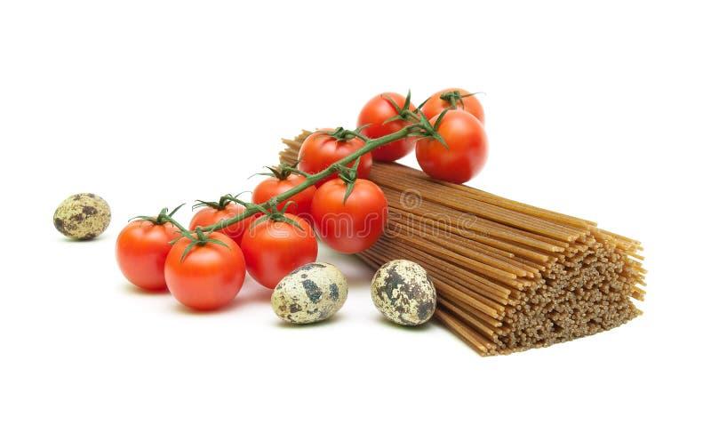 Vaktelägg, körsbärsröda tomater och spagetti som isoleras på vitbaksida fotografering för bildbyråer