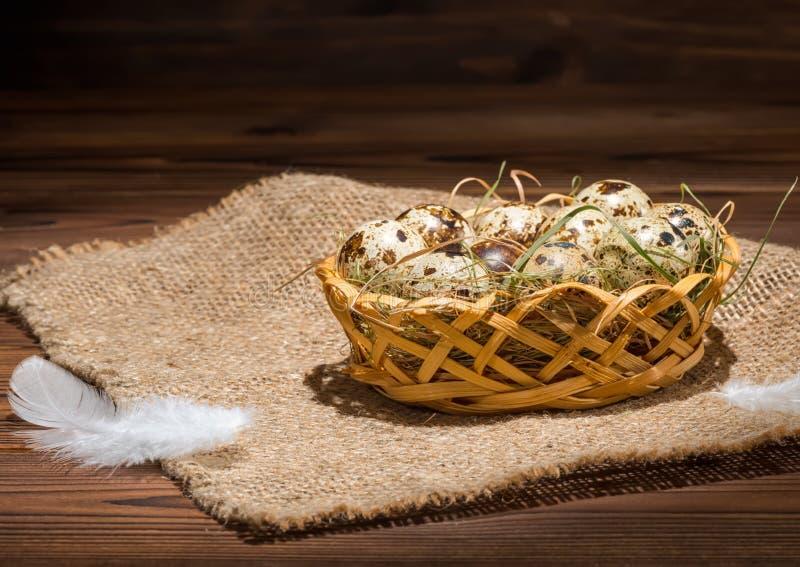 Vaktelägg med sugrör och fjädrar i korg på säckväv som är lantlig arkivfoton
