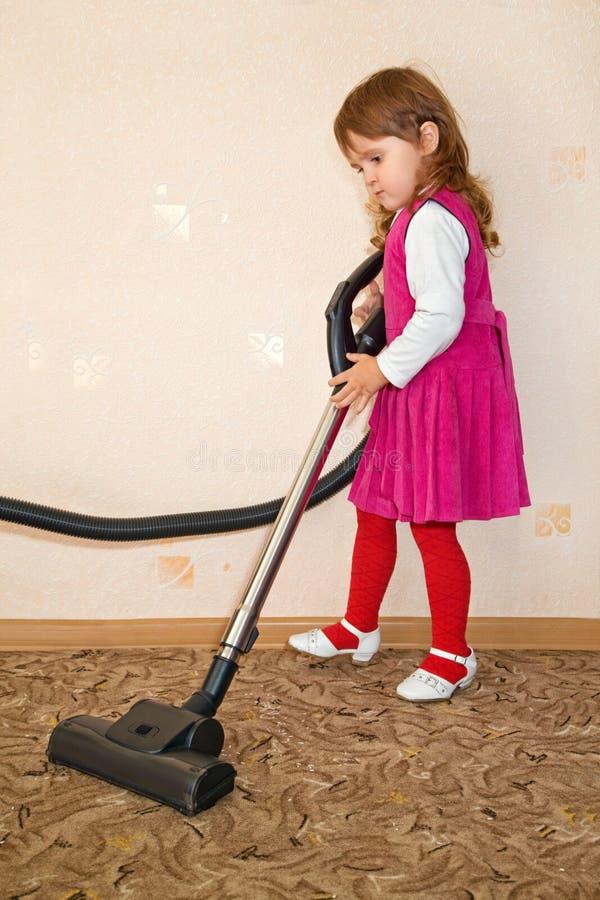 Vakuum des kleinen Mädchens ein Teppich stockfoto