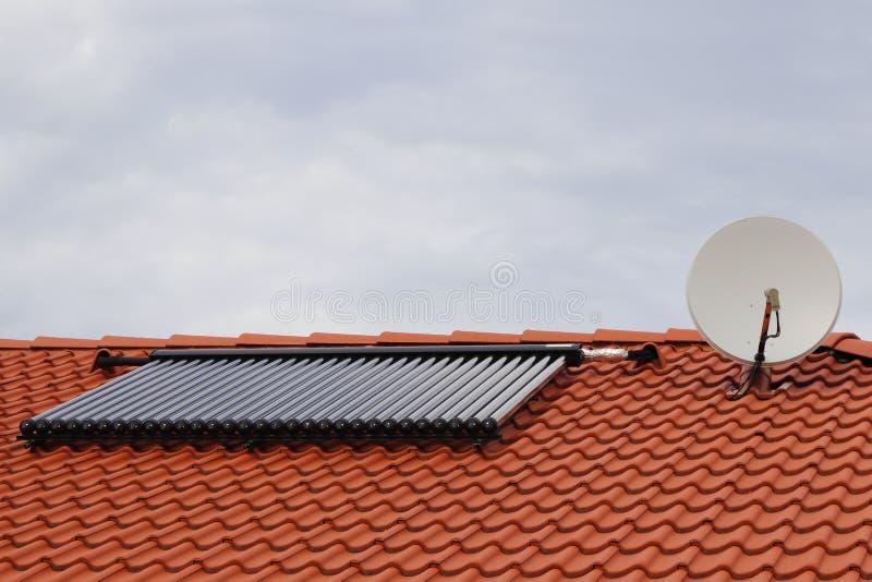 Vakuumkollektoren - Solarwarmwasserbereitungsheizsystem auf rotem Dach des Hauses mit Satelliten stockfotografie