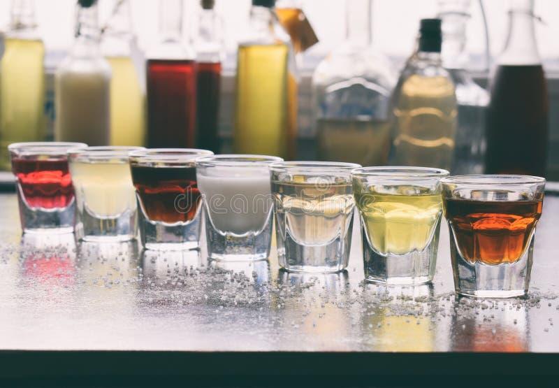 Val av alkoholdrycker Uppsättning av vin, konjak, likör, tinktur, konjak, whisky i exponeringsglas, flaskor Stor variation av alc arkivfoto