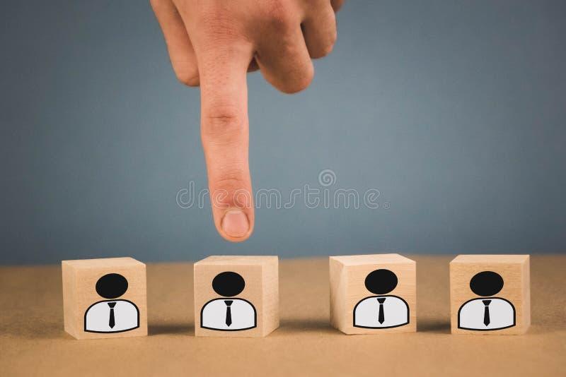 Val av en anst?lldledare fr?n folkmassan handpunkterna till träkuben som symboliserar att handen gör valet arkivfoto