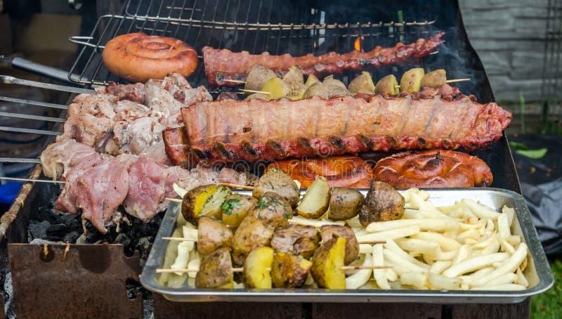 Val av kött som grillar över kolen på en bärbar grillfest med kryddiga korvar, nötköttkebaber och kuggar av stöd, utomhus arkivfoton