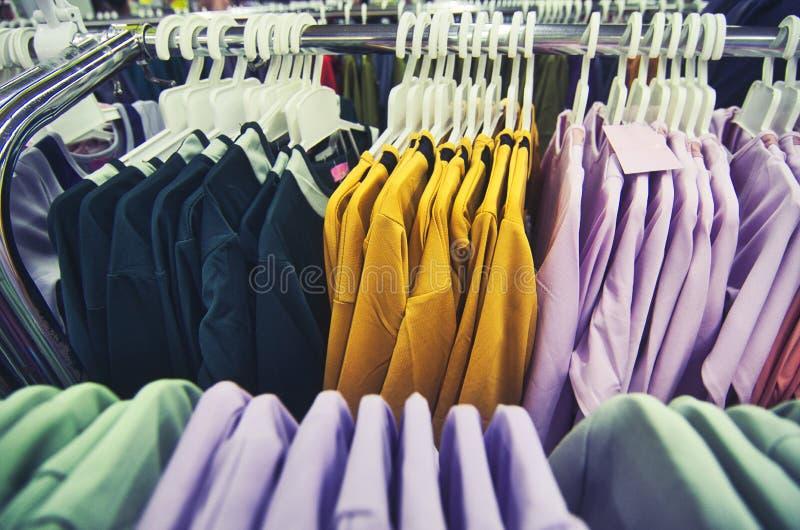 Val av kläder för kvinnor som hänger på hängare i shoppinggalleria royaltyfri fotografi