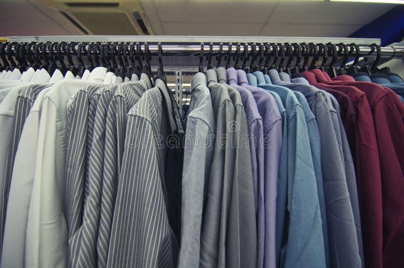 Val av kläder för män som hänger på hängare i shoppinggallerian för lagerförsäljningsbegrepp arkivbild