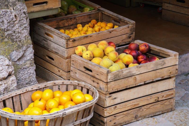 Val av ny mogen frukt i träaskar i en marknad royaltyfria bilder