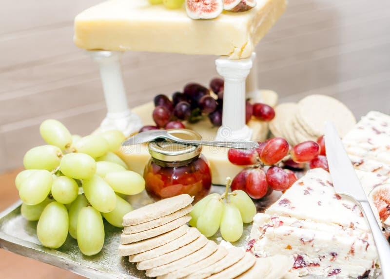 Val av ostar som framläggas på ett silveruppläggningsfat med hem gjord chutney royaltyfri foto