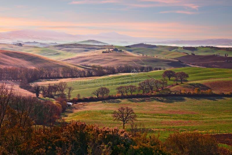 """Val d """"Orcia, Сиена, Тоскана, Италия: ландшафт на восходе солнца сельской ме стоковое фото rf"""