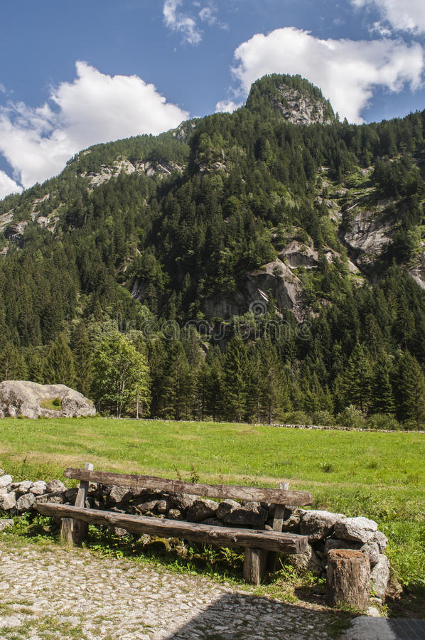 Val di Mello, Val Masino, Valtellina, Sondrio, Italy, Europe. Italy, 03/08/2017: a wooden bench in the Mello Valley, Val di Mello, a green valley surrounded by royalty free stock photo