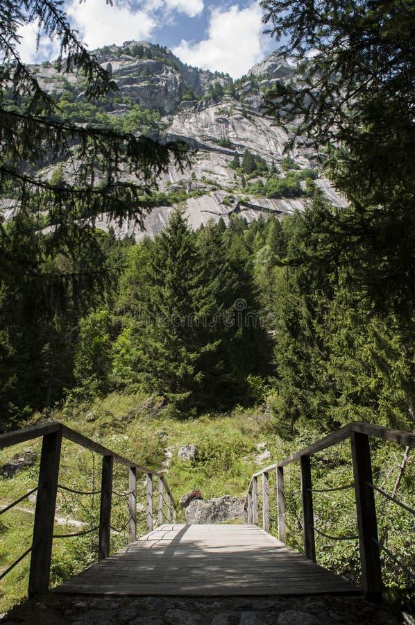 Val di Mello, Val Masino, Valtellina, Sondrio, Italy, Europe. Italy, 03/08/2017: wooden footbridge in the Mello Valley, Val di Mello, a green valley surrounded royalty free stock image