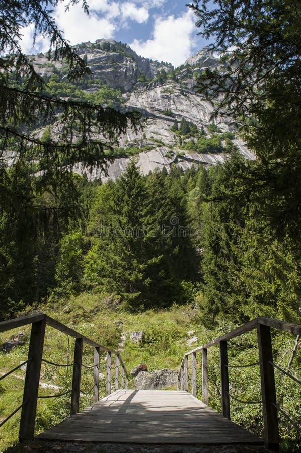 Val di Mello, Val Masino, Valtellina, Sondrio, Italy, Europe. Italy, 03/08/2017: wooden footbridge in the Mello Valley, Val di Mello, a green valley surrounded stock image