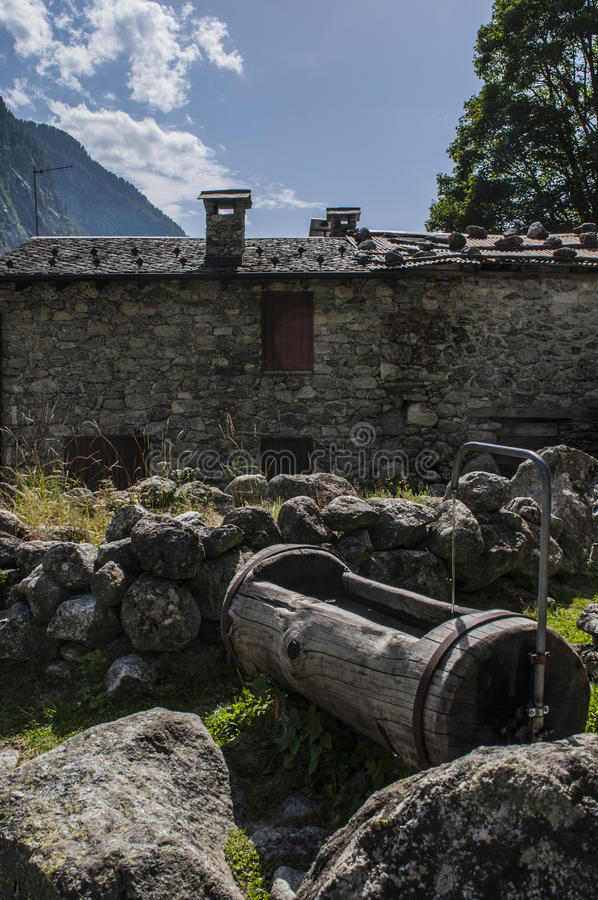 Val di Mello, Val Masino, Valtellina, Sondrio, Italy, Europe. Italy, 03/08/2017: a wooden fountain of spring water in the Val di Mello, green valley surrounded royalty free stock photos