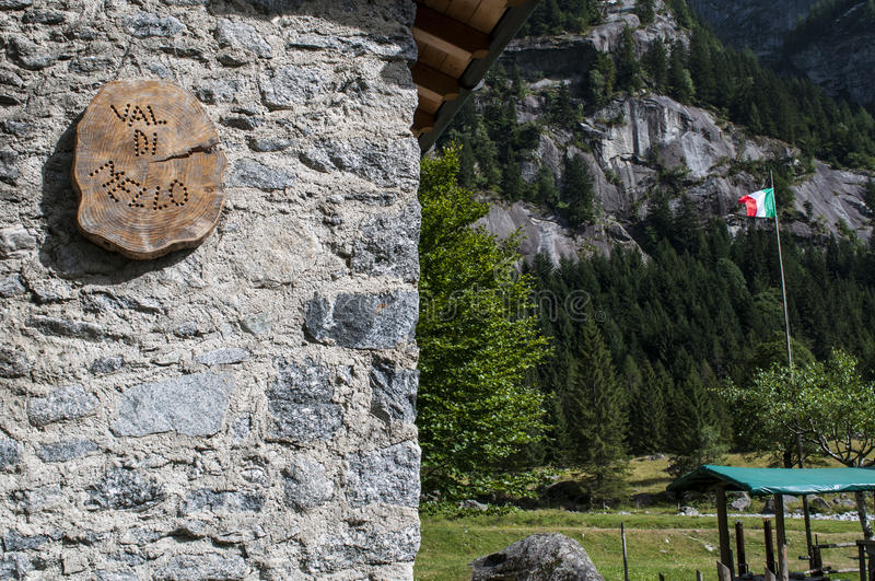 Val di Mello, Val Masino, Valtellina, Sondrio, Italy, Europe. Italy, 03/08/2017: wooden sign of the Mello Valley, Val di Mello, a green valley surrounded by royalty free stock images