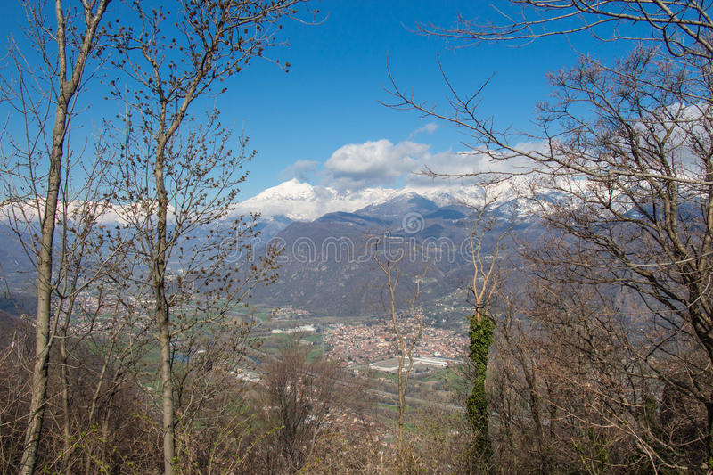 Val di Susa through branches with white alps on background. Piedmont. Italy royalty free stock photo
