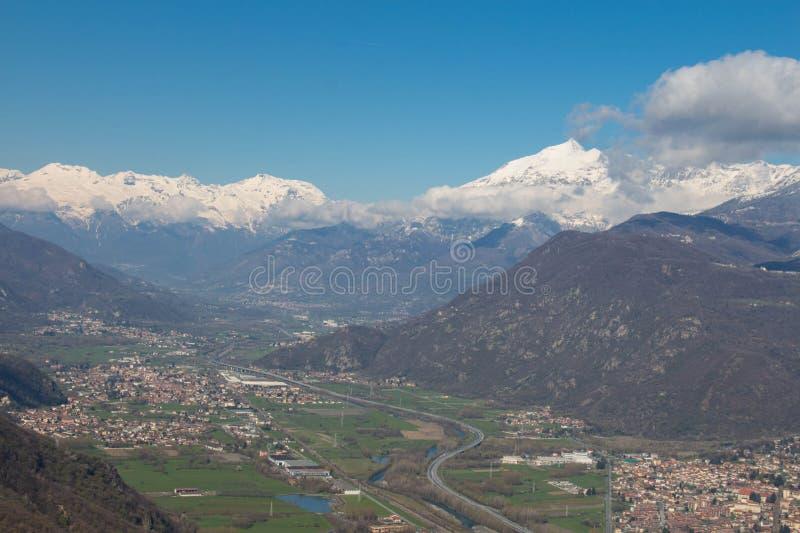 Val di Susa con sus pueblos y montañas nevosas en fondo piedmont Italia imagenes de archivo