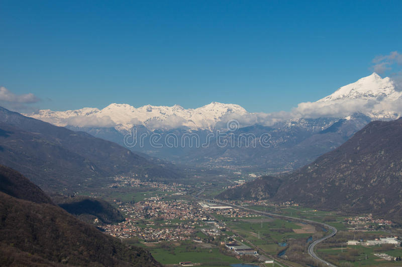 Val di Susa with its villages and snowy Alps on background. Piedmont. Italy stock photos