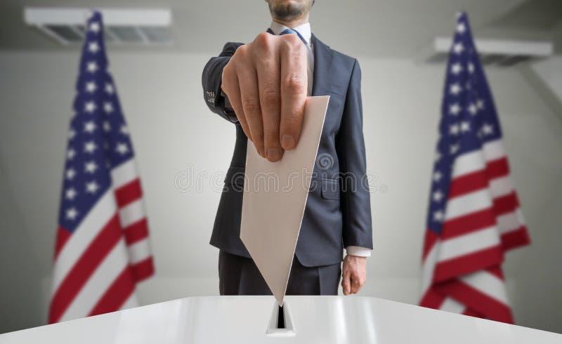 Val eller folkomröstning i Förenta staterna Väljaren rymmer kuvertet i hand ovanför sluten omröstning USA flaggor i bakgrund royaltyfri bild