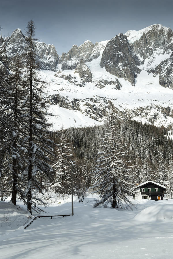 Val Ferret, mountain chalet in the snow among the trees royalty free stock image