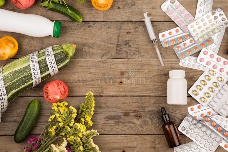 val mellan en sund livsstil och läkarbehandlingar, grönsaker eller preventivpillerar på det bruna träskrivbordet royaltyfri fotografi