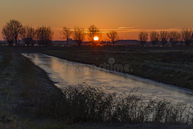A vala está congelada e o céu colore vermelho e alaranjado bonitos quando o sol aumenta sobre Zoetermeer imagem de stock