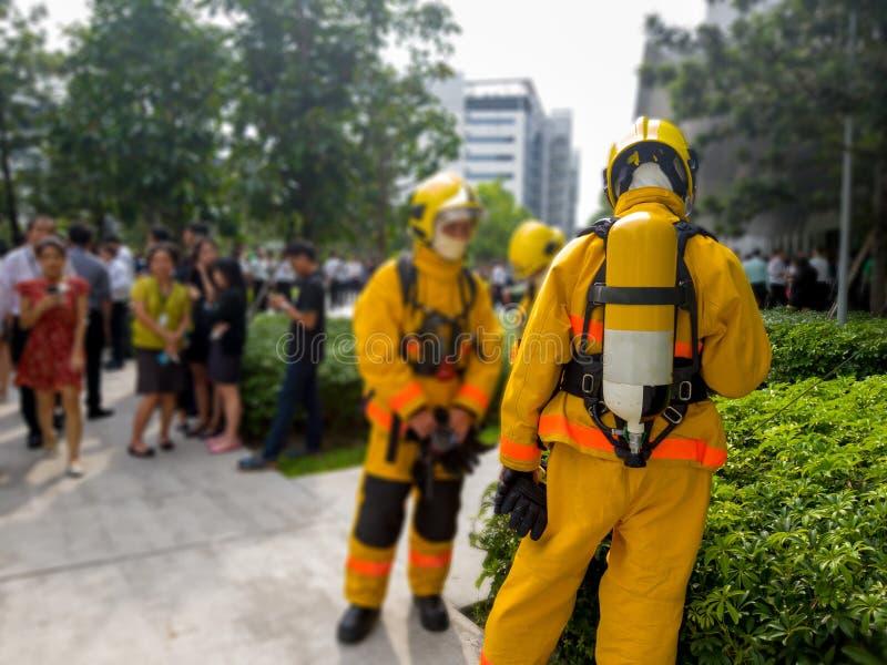 Vald fokus av tillbaka brandmän i gul dräkt med en syrebehållare i baksidan Brandmän undervisar kontorsarbetare till escaen arkivfoto