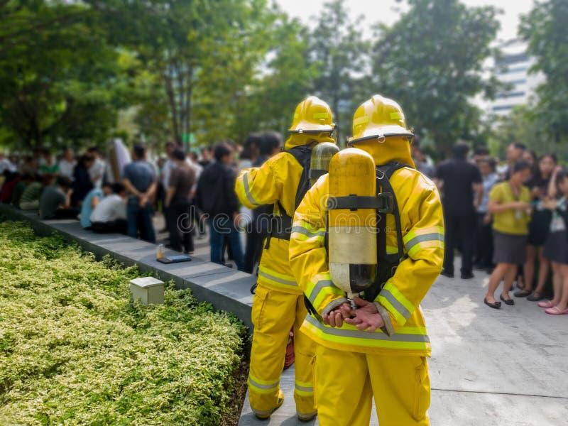 Vald fokus av tillbaka brandmän i gul dräkt med en syrebehållare i baksidan Brandmän undervisar kontorsarbetare till escaen arkivbild