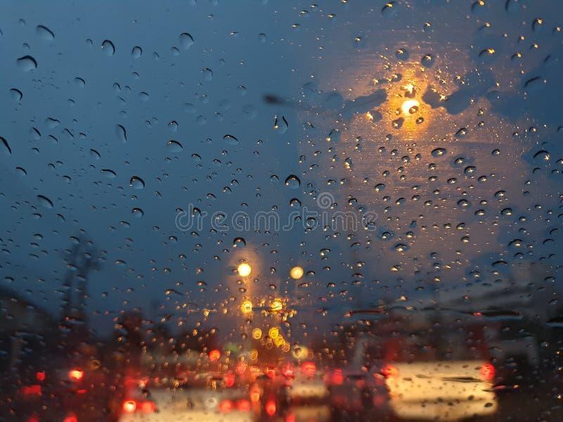 Vald fokusdroppe som är regnig på den glass bilen med nattljus arkivfoto