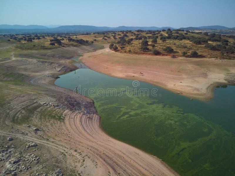 Valdecañas水库的鸟瞰图,用从海藻的绿色水和水的下降的自然线 ?? 免版税库存照片