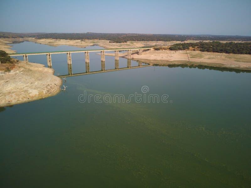 Valdecañas水库的鸟瞰图,用从海藻的绿色水和水的下降的自然线 ?? 免版税图库摄影