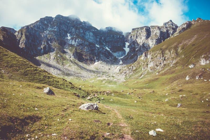 Vale bonito com um céu azul nebuloso e um trajeto que conduzem ao pico de montanha fotografia de stock royalty free