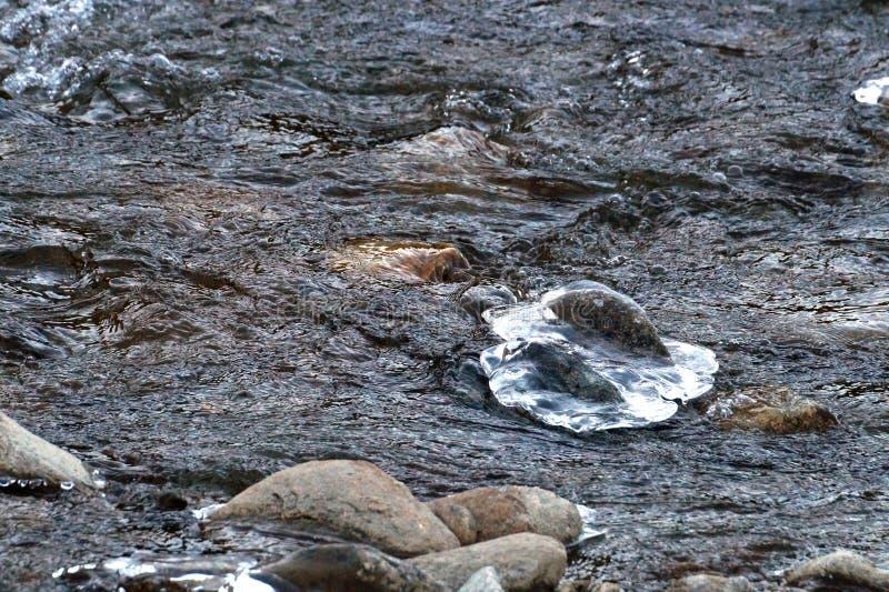 Vale do inverno do córrego congelado do rio da montanha coberto com o gelo e a neve no alvorecer colorido da luz do por do sol na fotos de stock