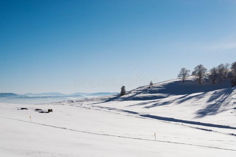 Vale nevado na parte superior da montanha com um céu azul claro em um dia ensolarado com flocos de neve de queda imagens de stock royalty free