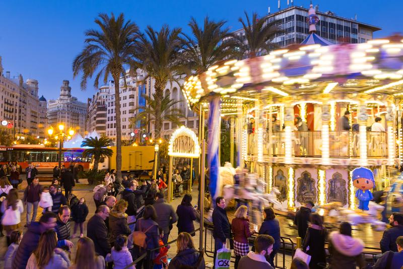 Christmas fair with carousel on Modernisme Plaza of the City Hall of Valencia, Spain. Valencia, Spain - Dec 16, 2017: People having fun in christmas spirit on royalty free stock images