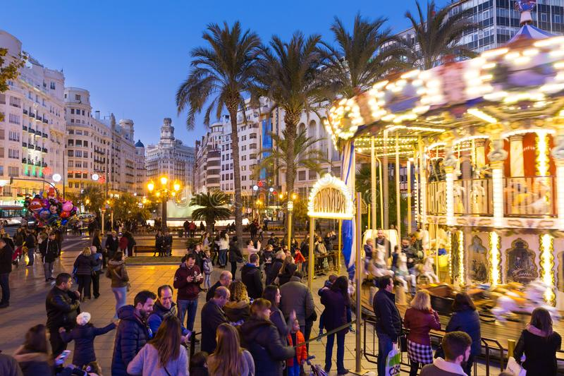 Christmas fair with carousel on Modernisme Plaza of the City Hall of Valencia, Spain. Valencia, Spain - Dec 16, 2017: People having fun in christmas spirit on royalty free stock photos