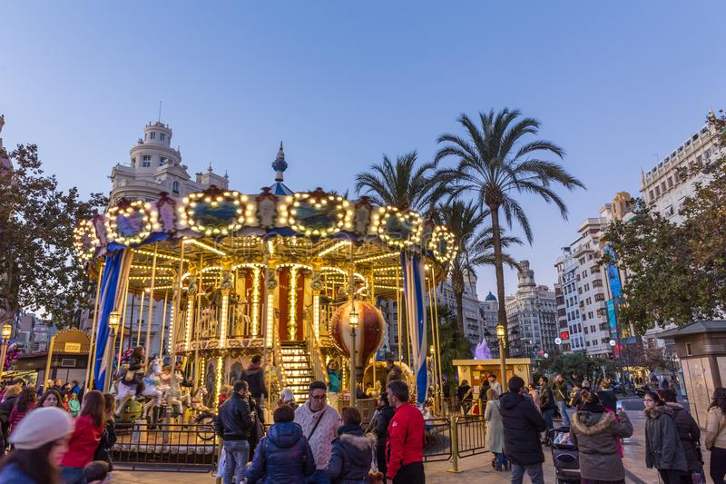Christmas fair with carousel on Modernisme Plaza of the City Hall of Valencia, Spain. Valencia, Spain - Dec 16, 2017: People having fun in christmas spirit on royalty free stock photo
