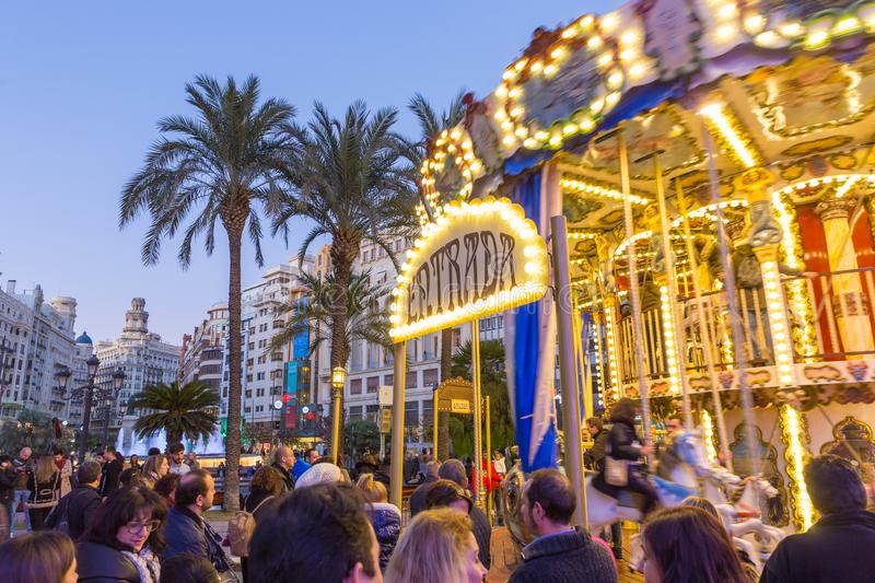 Christmas fair with carousel on Modernisme Plaza of the City Hall of Valencia, Spain. Valencia, Spain - Dec 16, 2017: People having fun in christmas spirit on stock images