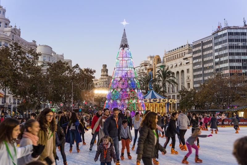 Christmas fair with people ice skating on Modernisme Plaza of the City Hall of Valencia, Spain. Valencia, Spain - Dec 16, 2017: People ice skating on Christmas royalty free stock image
