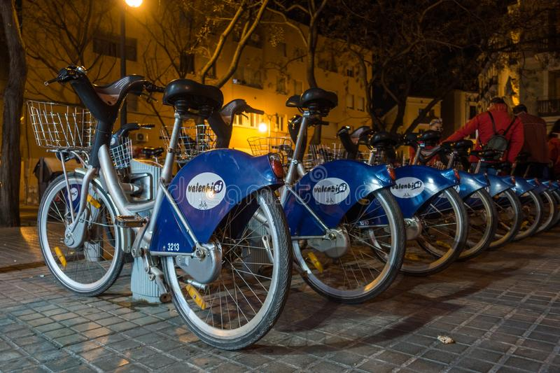 Bikes for hire at night in Valencia Spain on February 24, 2019. Four unidentified people. VALENCIA, SPAIN - FEBRUARY 24 : Bikes for hire at night in Valencia stock photos