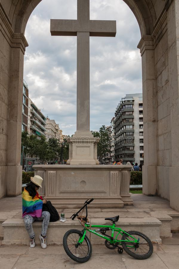 Valencia, Spain - June 16, 2018:  An assistant to gay pride day parade rests next to a large cross stock images