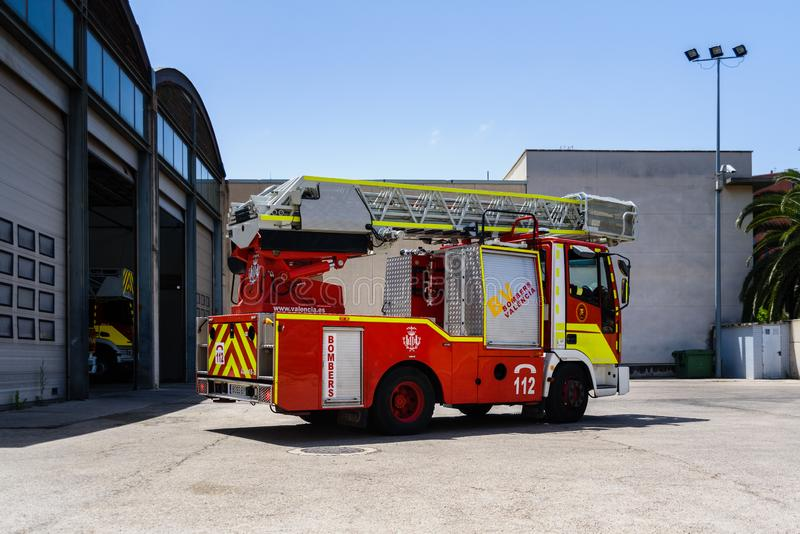 Valencia, Spain - June 8, 2019: Fire truck with ladder leaving the fire station to help in an emergency stock photo